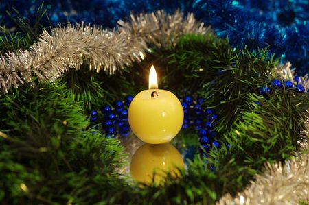 A close view of a candle and some big sparkly christmas tree decorations.
