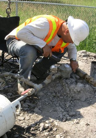 Young Hydrogeologist Field Engineer taking packer test for underground soil layers water flow.