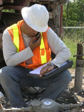 packer: Young Hydrogeologist Field Engineer in phone conversation with head office over unusual results from packer test for underground soil layers water flow. Stock Photo