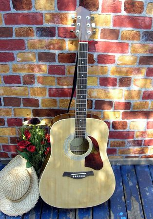 Country music. Guitar, flower and country hat on the porch resting after short country music concert for friends during  Stock Photo