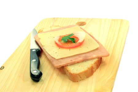 bred: Simple Sandwich over wooden serviette. Euro Style Bred, Margarine, Slices Ham, Yellow cheese,  Tomato, Onion and Sprig Parsley. Stock Photo