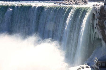 Niagara Falls - Canada. Canadian part of the Falls of Niagara river over the Niagara Escarpment with noticeable cloud of water mist and snow bridge over Niagara River.