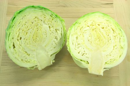 two and a half: Cabbage ready to be chopped for cooking. Picture of cut on two half a head of cabbage over wooden plank.