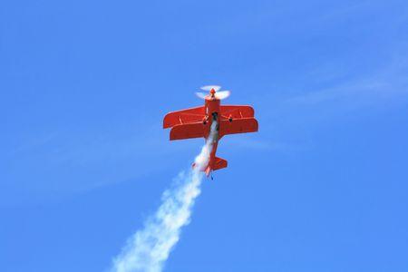demonstrative: Aerobatics flight. Double-wings sport aeroplane perform demonstrative aerobatics flight with smog track. Stock Photo