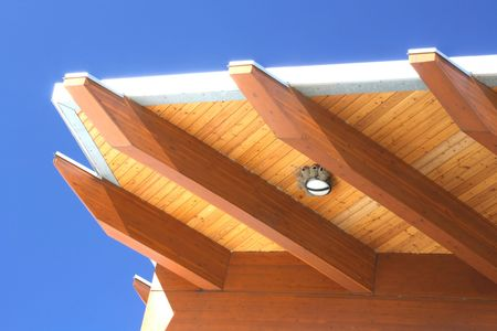 Modern roof architecture detail on the blue sky background, visible are bird nests around the lighting fixture.