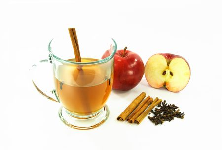 Glass of hot apple cider spiced with cinnamon stick and cloves - spices cinnamon sticks, cloves and raw apples for preparing the drink are shown separately on the picture too.  Stock Photo