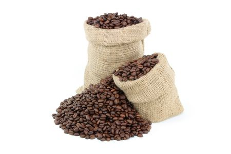 Roasted coffee beans over white. Still picture displaying roasted coffee beans spilled on pile and in burlap sacks over white background.