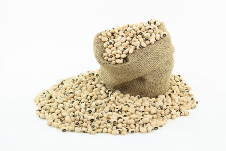 Black Eyed Peas over white background. Picture of raw (not cooked) Black Eyed Peas (beans) in burlap sack and on pile over white background.