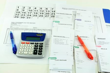 Picture of all expense report forms, daily and monthly, electronic calculator, pens and bills used to finalize financially the month - getting ready to fill down daily and monthly expense reports.   Stock Photo