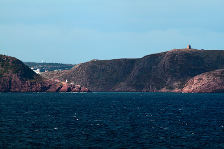 national historic site: Approach to St  Johns Harbor - Prehistoric rock Signal Hill, with Cabot Tower on top  presently National Historic Site with rich communication and military history , part of town, Fort Amherst