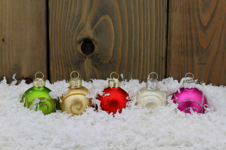 upper half: Christmas  New Year, Holiday Season  Decoration  Decorative colorful balls in line over the snow  very suitable for Greeting Card  space for text in upper half of picture    Stock Photo