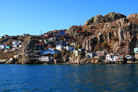 east end: From the Atlantic Ocean level View over Newfoundland Capital St Johns Houses on East end which are reaching the foot steps of million years old rock of Signal Hill  Stock Photo