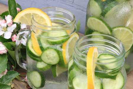 In hot summer day on the table decorated with apple tree blooms in backyard is served Naturally Flavored Infused Cucumber water with ice and lemon and lime slides photo