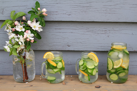 In hot summer day on the table decorated with apple tree blooms is served Naturally Flavored (Infused) Cucumber water with ice cubs, lemon, lime slides in Glass Jars photo