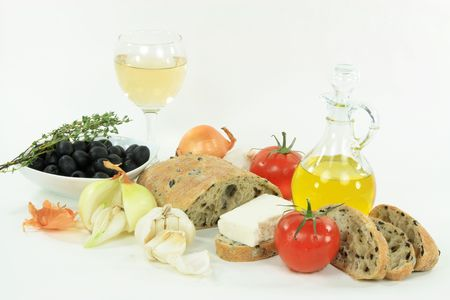 Healthy Mediterranean lunch. Sliced Loaf Mediterranean Ciabatta  olive bread, olives, oil, garlic, feta cheese, onion, glass of wine and tomatoes over white background.  Stock Photo