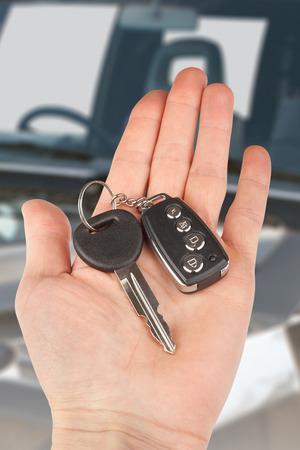 thumb keys: car key with alarm in hand over auto Stock Photo