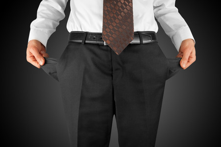 bankrupt business man showing empty pockets  hands
