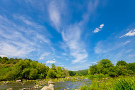 peaceful background: Bue sky with clouds over river. Nature in vibrant color Stock Photo
