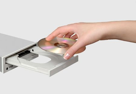 dvdr: Female hand inserting a CD into a compact disk drive