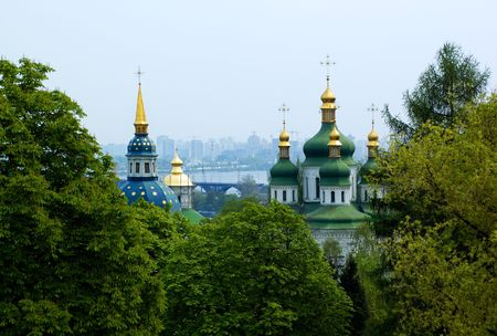 Golden christian church domes and christian crosses covered with trees riligious background photo