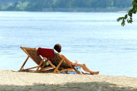Man and woman in chairs resting on the river beach photo