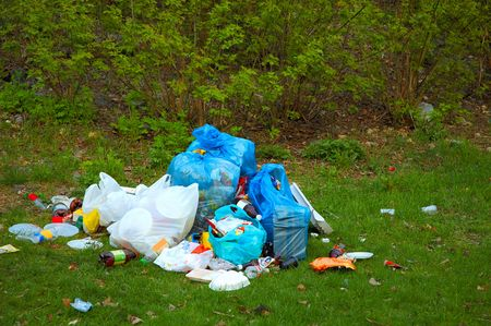 Pile of garbage on green grass in the nature environment problems Stock Photo