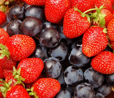 Colorful strawberries and grapes macro organic background vitamins concept photo