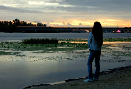 Woman alone standing on bank of river watching sunset photo