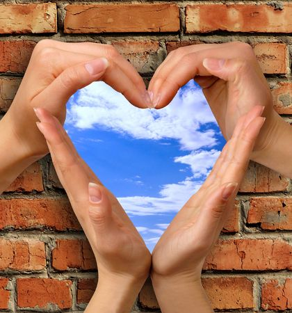 imprison: Heart symbol made from hands over a brick with a window into blue sky conceptual photo illustration Stock Photo