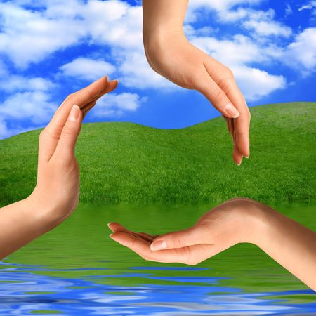 Recycling symbol made from hands on summer nature background Environment and ecology artistic concept photo