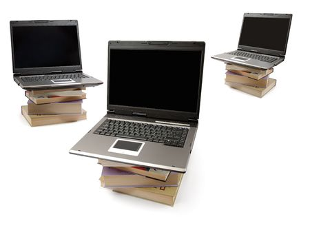 Laptop computers standing on piles of books. Information and education concept photo