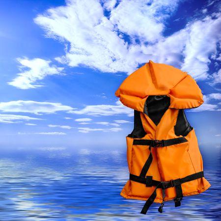Orange life vest rescue jacket over blue summer seascape background photo
