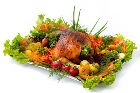 Roasted chicken and vegetables on a tray isolated on white background