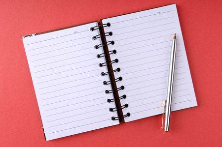 Open notepad with a pen. Isolated on red background. photo