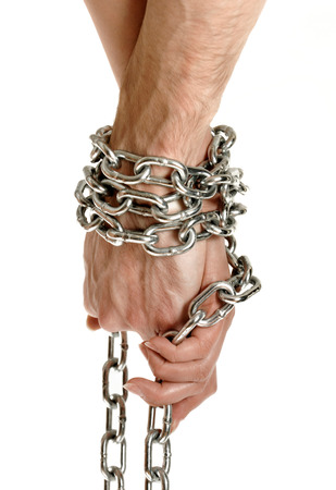 Closeup of couple hands tied together with a chain conceptual photo isolated on white background photo