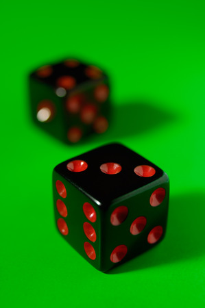 Pair of black dice isolated on green background photo