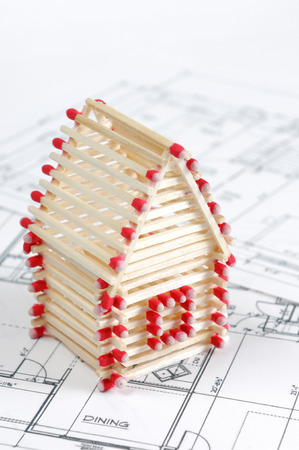 House made from matches standing on construction plans Construction industry Home renovation Real estate agency Architectural design concept Stock Photo - 28791046