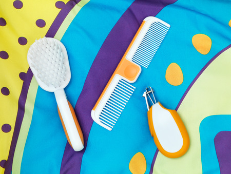 clippers comb: Brush, comb, nail clippers, set of baby grooming accessories on colorful fabric