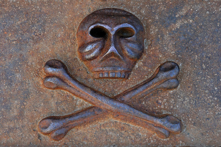 cast iron: Rusty human skull with crossed bones cast from iron Danger and death symbol