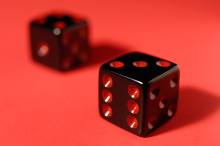 Pair of black dice isolated on red background photo