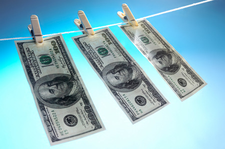 Hundred dollar bills drying on a clothes line isolated on blue sky background Money laundering concept photo