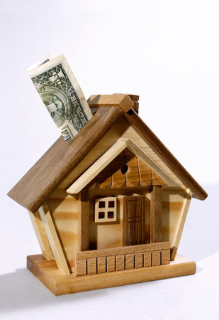 Dollar bill being deposited into a house money box. Investment, real estate, mortgage concept photo