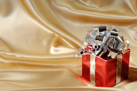 red gift box: Red gift box with a silver bow on golden background Stock Photo