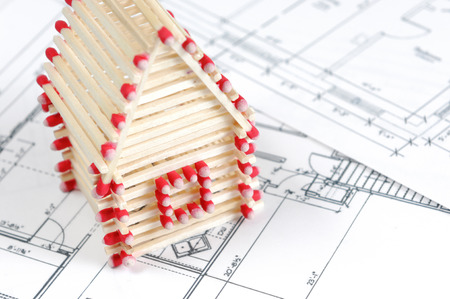 House made from matches standing on construction plans Construction industry Home renovation Real estate agency Stock Photo - 28767601