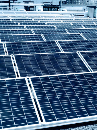 solar array: Array of solar panels in rows on a roof of a building in a city