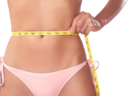 Junge Frau, die ihre Taille mit einem Maßband, Nahaufnahme der Bauch isoliert auf weißem Hintergrund