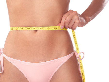 midsection: Young woman measuring her waist with a measuring tape, closeup of stomach isolated on white background