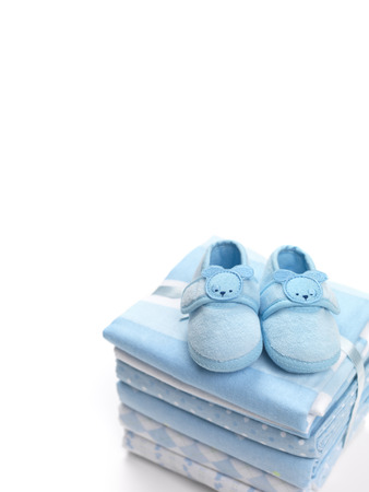 swaddling clothes: Cute blue baby boy shoes on a pile of swaddling blankets isolated on white background