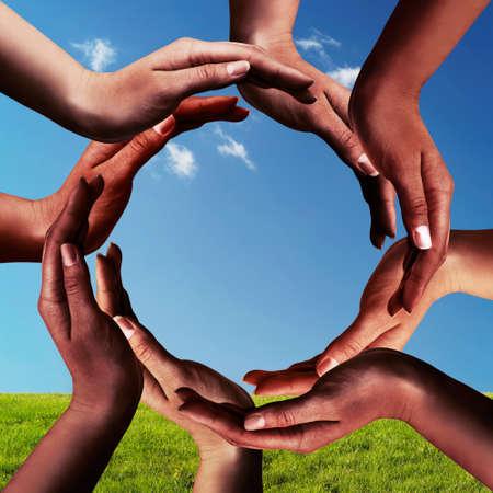 sostenibilidad: La paz y el símbolo de la unidad conceptual de las diferentes manos negro Africano haciendo un círculo juntos en el cielo azul y la hierba verde de fondo