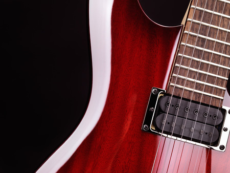 Closeup of red electric guitar neck, strings and pickup photo